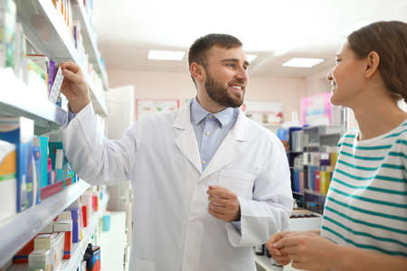 Professional pharmacist working with customer in modern drugstore