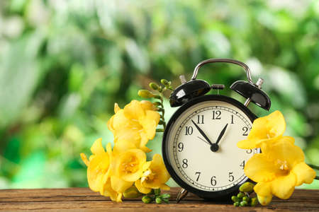 Alarm clock and beautiful spring flowers on wooden table. Time change concept Stock Photo