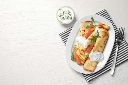Delicious thin pancakes with salmon and sour cream on white wooden table, flat lay. Space for text