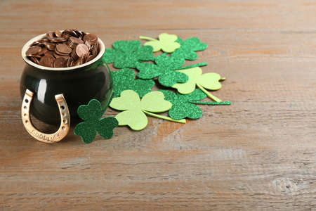 Pot of gold coins, horseshoe and clover leaves on wooden table. St. Patrick's Day celebration