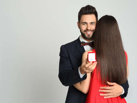 Man with engagement ring making marriage proposal to girlfriend on light grey background. Space for text Archivio Fotografico
