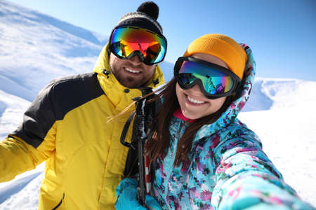Couple taking selfie on hill. Winter vacation