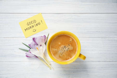 Delicious coffee, flowers and card with GOOD MORNING wish on white wooden table, flat lay