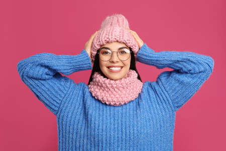 Young woman wearing warm sweater, snood and hat on crimson background. Winter season Foto de archivo