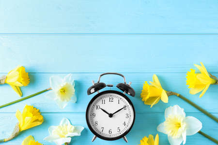 Black alarm clock with spring flowers and space for text on light blue wooden background, flat lay. Time change Stock Photo