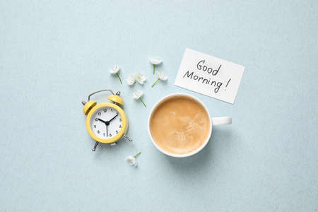 Flat lay composition with message GOOD MORNING and coffee on light blue background