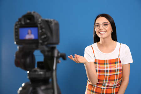 Young blogger recording video on camera against blue background
