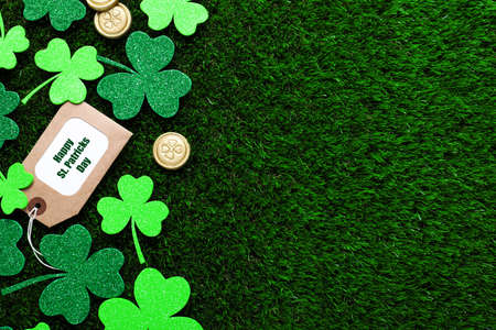 Flat lay composition with clover leaves and gold coins on green grass, space for text. St. Patrick's Day celebration