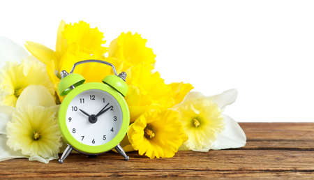 Green alarm clock and spring flowers on wooden table against white background. Time change