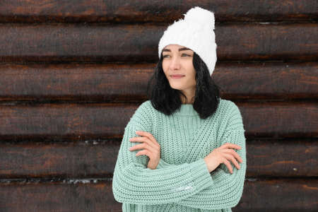 Young woman wearing warm sweater and hat near wooden wall. Winter season Banque d'images