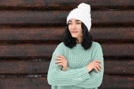 Jeune femme portant un pull chaud et un chapeau près d'un mur en bois. L'hiver Banque d'images
