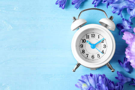 White alarm clock, spring flowers and space for text on light blue wooden table, flat lay. Time change