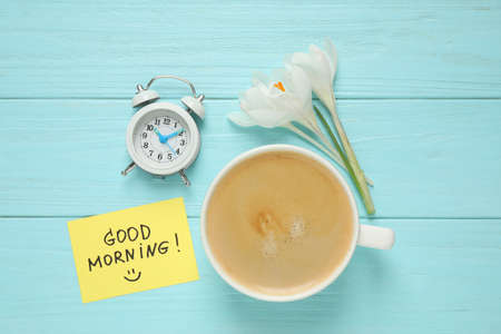Delicious coffee, alarm clock, flowers and card with GOOD MORNING wish on light blue wooden table, flat lay