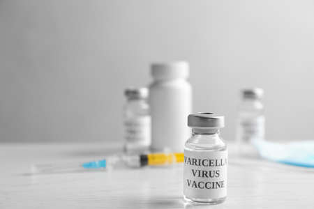 Chickenpox vaccine and syringe on white wooden table, space for text. Varicella virus prevention Stock Photo