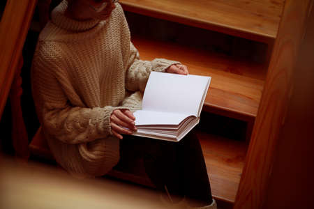 Woman reading book on wooden staircase, view from above Stock Photo