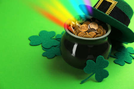 Pot with gold coins, hat and clover leaves on green background, space for text. St. Patrick's Day celebration