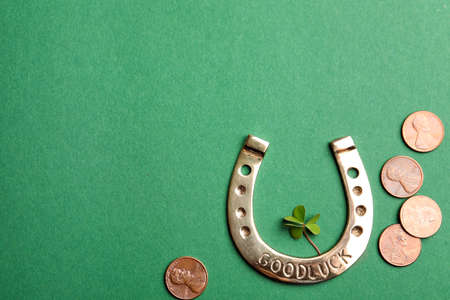 Flat lay composition with horseshoe on green background, space for text. St. Patrick's Day celebration