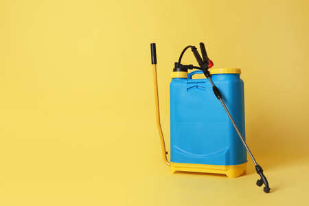 Manual insecticide sprayer on yellow background, space for text. Pest control
