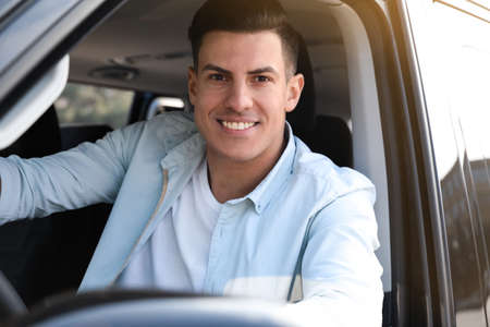 Handsome man driving his modern car, view from outside Stock fotó