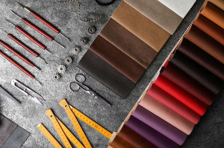 Flat lay composition with leather samples and craftsman tools on grey stone background