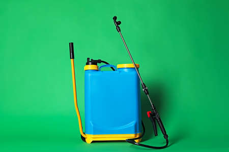 Manual insecticide sprayer on green background. Pest control Stock Photo