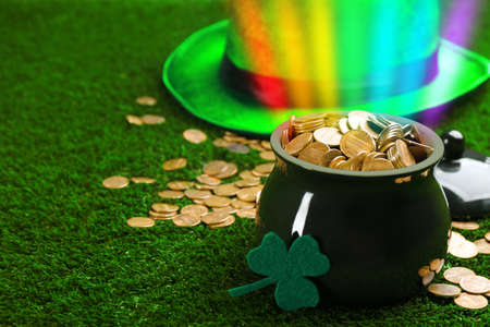 Pot with gold coins, hat and clover on green grass, space for text. St. Patrick's Day celebration