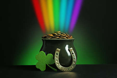 Pot with gold coins, horseshoe and clover on table against dark background. St. Patrick's Day