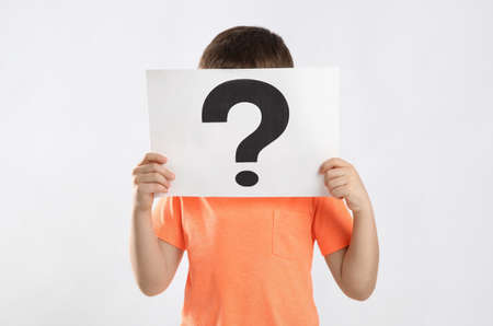 Little boy holding paper with question mark on white background
