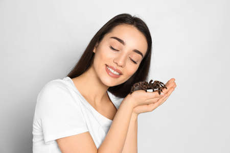 Woman holding striped knee tarantula on light background. Exotic pet