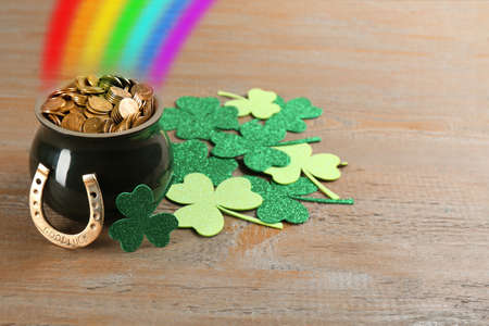 Pot with gold coins, horseshoe and clover leaves on wooden table. St. Patrick's Day celebration