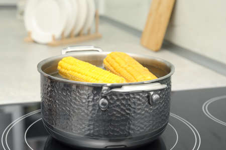 Pot with boiling corn on induction cooktop