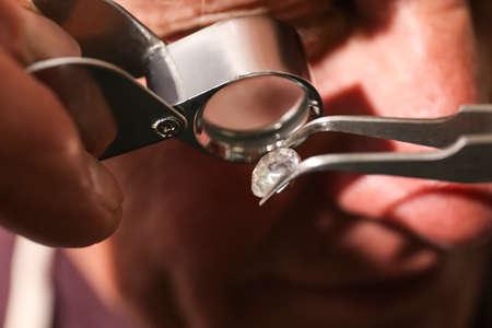 Professional jeweler evaluating beautiful gemstone, closeup view