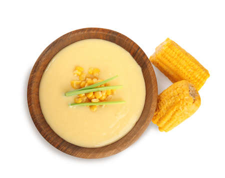 Delicious corn cream soup and cobs on white background, top view