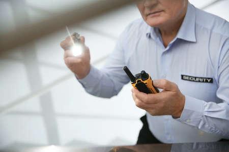 Professional security guard with flashlight and portable radio set indoors, closeup Foto de archivo