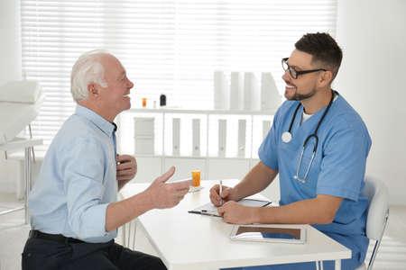 Doctor examining senior patient in modern office