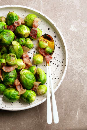 Delicious Brussels sprouts with bacon on marble table, top view