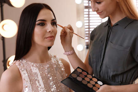 Professional makeup artist working with beautiful woman in salon