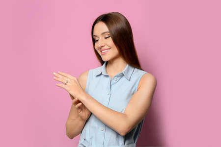 Happy young woman wearing beautiful engagement ring on pink background Archivio Fotografico
