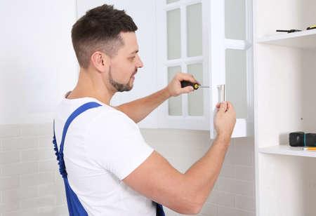 Worker installing handle of cabinet door with screwdriver in kitchen