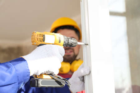 Workers using electric screwdriver for window installation indoors, closeup