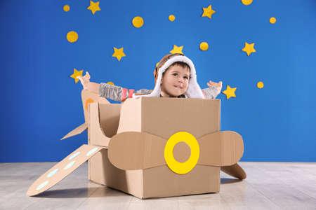 Mignon petit enfant jouant avec un avion en carton près du mur bleu
