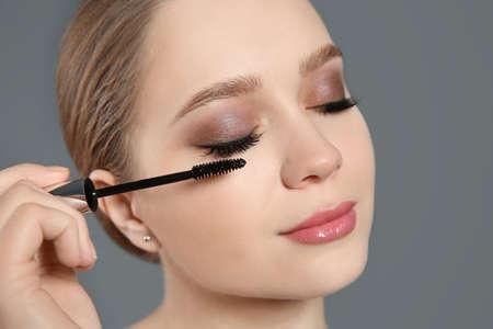 Beautiful woman applying mascara on light grey background. Stylish makeup Zdjęcie Seryjne