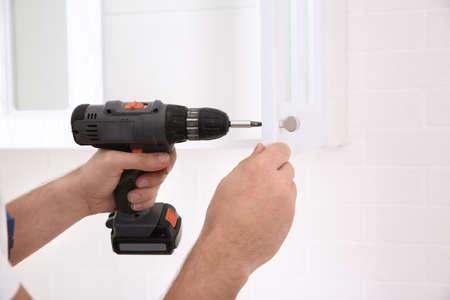Worker installing handle on cabinet door with screw gun in kitchen, closeup