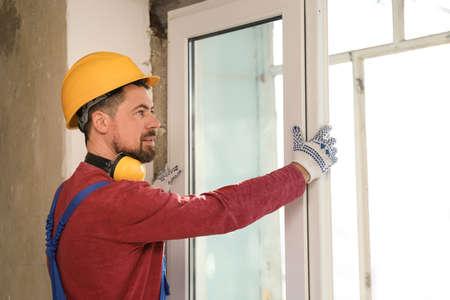 Worker in uniform installing plastic window indoors