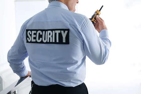 Professional security guard with portable radio set indoors, closeup 免版税图像