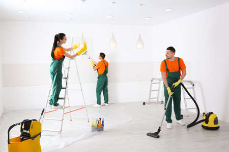 Team of professional janitors cleaning room after renovation