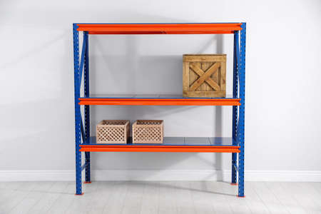 Metal shelving unit with wooden crates near light wall indoors