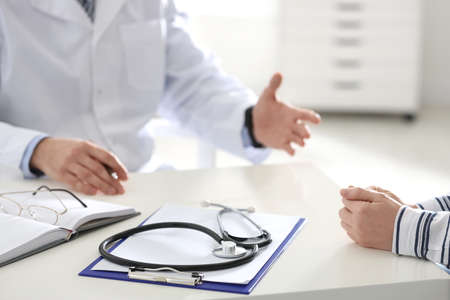 Doctor consulting patient at desk in clinic, closeup