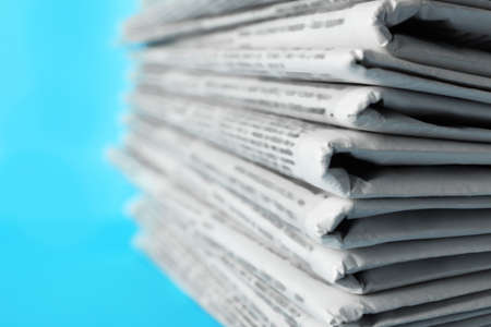 Stack of newspapers on light blue background, closeup. Journalist's work Banque d'images
