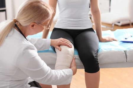 Female orthopedist applying bandage onto patient's knee in clinic Standard-Bild